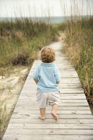toddler walking: Caucasian male toddler walking on beach access walkway toward beach.