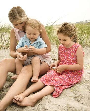 Caucasian mid-adult woman sitting with male toddler on lap and beside Caucasian female child on beach  looking at shells. photo