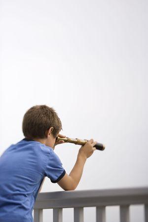 snoop: Caucasian pre-teen boy leaning on railing looking through telescope. Stock Photo