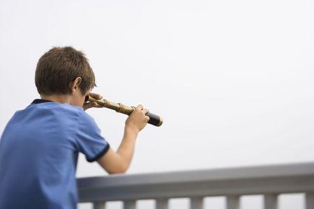 preteen boy: Du Caucase pr�-adolescent gar�on pench� sur la balustrade en regardant � travers t�lescope.