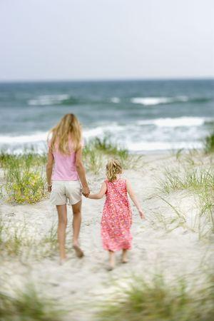 Caucasian pre-teen girl holding hands with child walking toward beach. photo