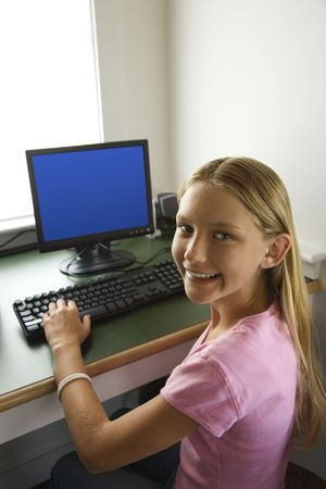 Caucasian pre-teen girl at computer looking over shoulder smiling at viewer. Stock Photo - 2478794