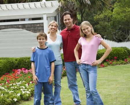 bald girl: Caucasian family of four posing for portrait in yard. Stock Photo