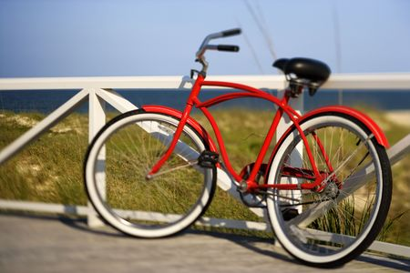 beach cruiser: Red beach cruiser bicycle leaning against walkway rail on beach on Bald Head Island, North Carolina.