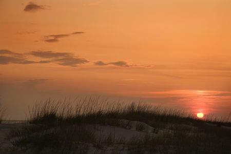 bald head island: Sun setting over beach sand dune on Bald Head Island, North Carolina.
