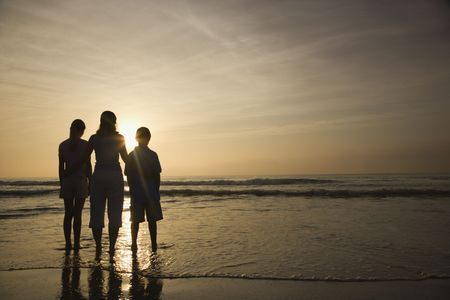 Caucasian mid-adult mother and teenage kids standing silhouetted on beach at sunset. photo