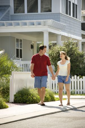 suburbs: Caucasian mid-adult  couple walking on suburban sidewalk holding hands. Stock Photo