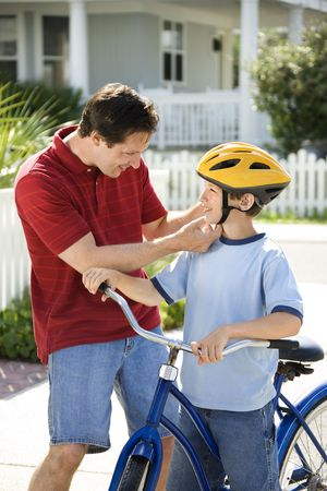 strapping: Caucasian mid-adult dad strapping bicycle helmet on pre-teen son.