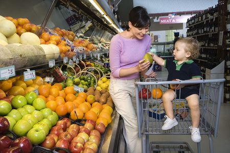 Caucasian mid-adult woman grocery shopping for fruit with young male toddler. photo