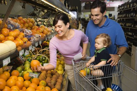 Caucasian mid-adult parents grocery shopping for fruit with male toddler. photo