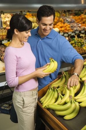Caucasian mid-adult couple grocery shopping for bananas. photo
