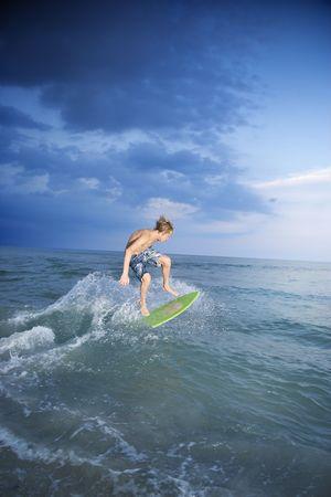 only one teenage boy: Caucasian male teen riding skimboard. Stock Photo