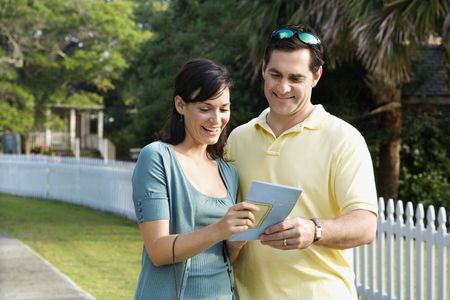 bald head island: Mid-adult Caucasian couple holding a map and smiling. Stock Photo