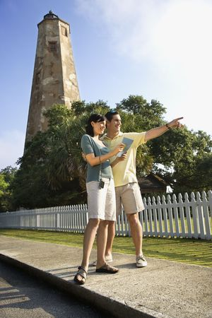 bald head: Mid-adult Caucasian couple sightseeing with lighthouse in background at Bald Head Island, North Carolina.