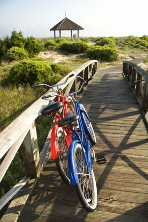 Image of red and blue bike leaning against railing of boardwalk.  photo