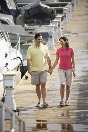 MId-adult Caucasian couple holding hands and walking at harbor.  photo