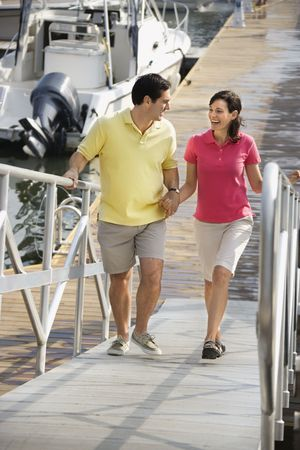 Mid-adult Caucasian couple holding hands and walking up ramp at harbor.  photo