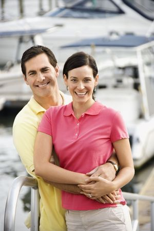 Portrait of Caucasian mid-adult couple embracing at harbor.  photo