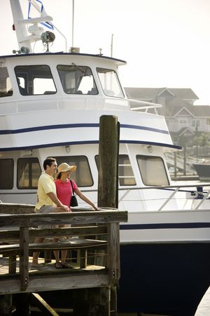 Mid-adult Caucasian couple at dock with boat in background. photo