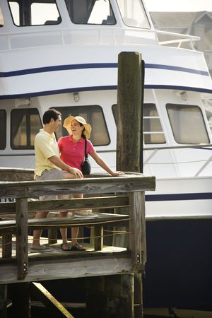 Mid-adult Caucasian couple at dock looking at each other with boat in background. photo