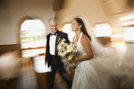 Bride and groom leaving church with motion blur effect. photo