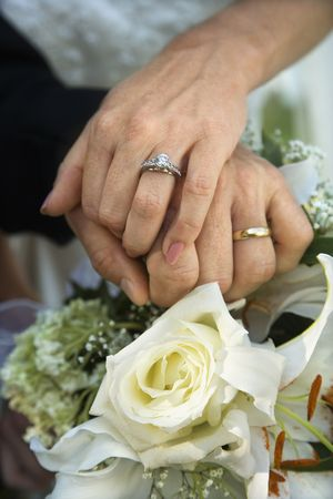 Close up image of bride and grooms hands overlapping. photo