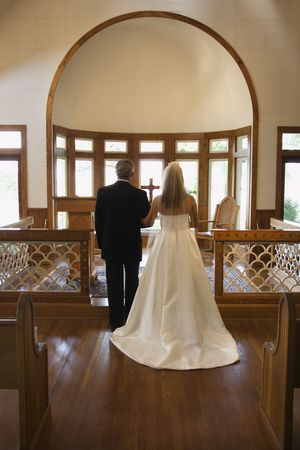 Portrait of bride and groom at alter of a church. photo