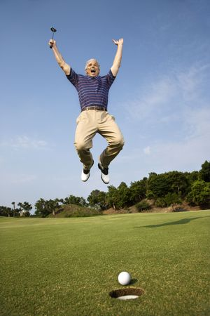 the hole: Caucasion mid-adult man holding golf club jumping in air cheering with golfball and hole in foreground.