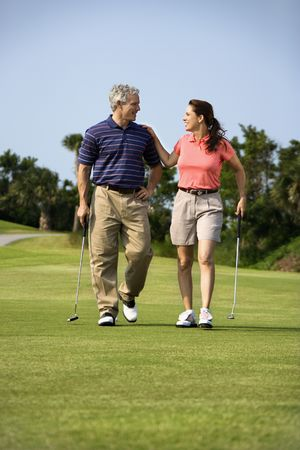 Caucasion mid-adult man and woman walking on golf course talking to each other. photo