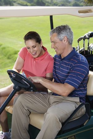 golf cart: Mid-adult male and female in golf cart pointing at score card.