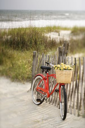 coast: Red vintage bicycle with basket and flowers leaning against wooden fence at beach.