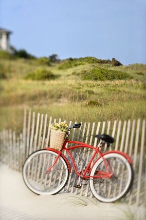 baskets: Red vintage bicycle with basket and flowers leaning against wooden fence at beach.