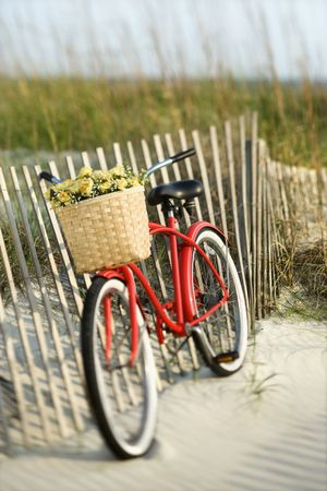 Red vintage bicycle with basket and flowers leaning against wooden fence at beach. Stock Photo - 2231818