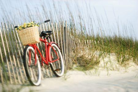 bicicleta retro: Rojo bicicleta con canasta de la vendimia y flores lleaning contra la valla de madera en la playa.