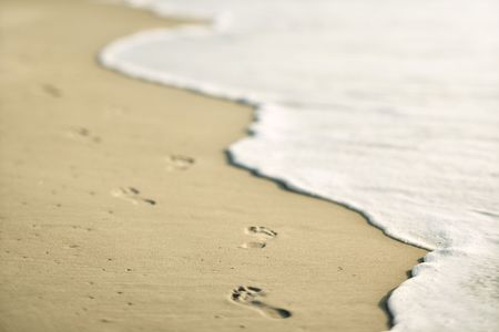 Scenic sandy coastline with footprints and waves. photo