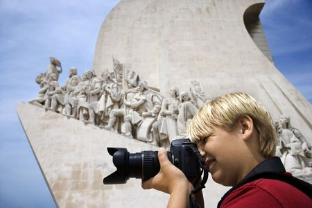 discoveries: Caucasian boy looking through camera at the Monument to the Discoveries in Lisbon, Portugal. Editorial