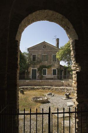 passageway: View of Italian dwelling through arched masonry passageway.