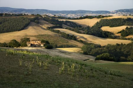 Rolling hills and building in countryside in Tuscany, Italy. photo