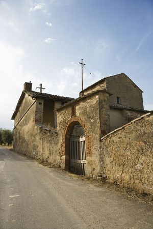disrepair: Old stone buillding in state of disrepair with arched gated entrance in Tuscany.