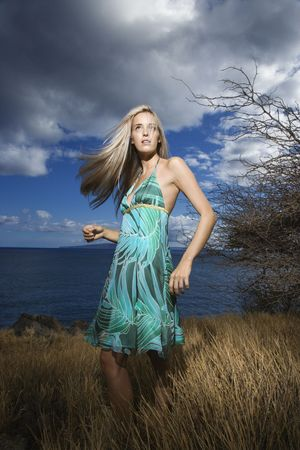 Caucasian young adult blond woman standing in field on coast with hair swinging out. photo