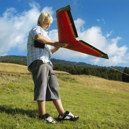 grassy knoll: Pre-teen Caucasian male preparing to fly remote controlled airplane on grassy knoll.