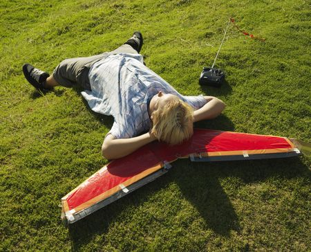 grassy knoll: Pre-teen Caucasian male laying and resting his head on airplane and grassy knoll.