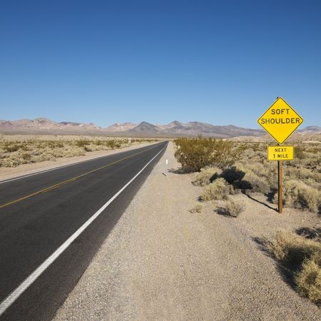 road shoulder: Road in desert with sign for soft shoulder and mountains in distance.