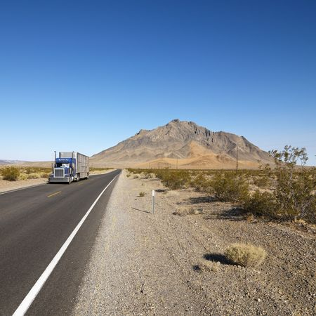 18 wheeler: Tractor trailer driving on desert road with mountain in background.