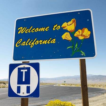 highway signs: Welcome to California sign with strip of highway and clear blue sky in background.  Stock Photo