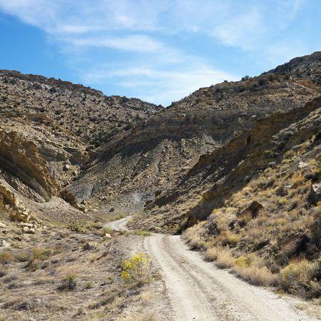Dirt road winding through rocky desert cliffs of Cottonwood Canyon, Utah. photo