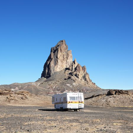 RV travelling toward rock formation in the desert of Monument Valley, Utah. Stock Photo - 2236269