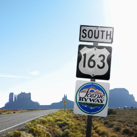 Sign for Scenic Byway 163 south beside road with rock formations in background in Monument Valley, Utah. photo