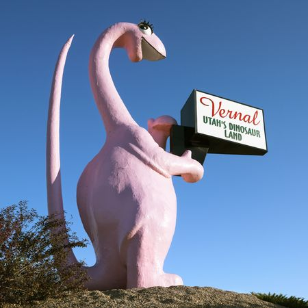 vernal: Pink dinosaur holding sign for city of Vernal, Utah.