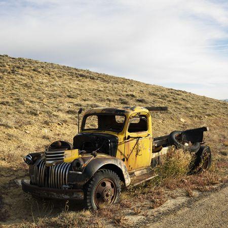 pickup truck: Antiguo amarillo destartalada camioneta sentado abandonados en colina.